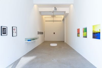 The long, narrow gallery space of Marfa' Projects in Beirut features artworks lined upon the wall, including a series of photographs taken through blue and yellow tinted glass to the right-hand side of the space.