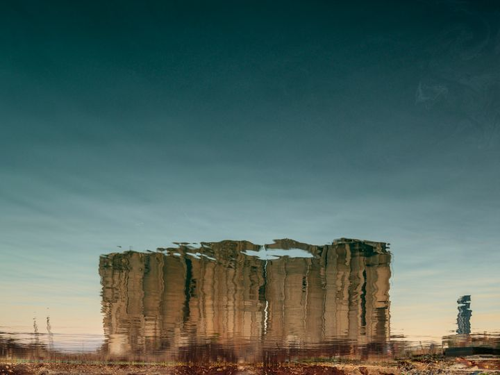 In a photograph by Dia Mrad, the reflection of a destroyed silo is photographed in a body of water, so that it appears upside down.