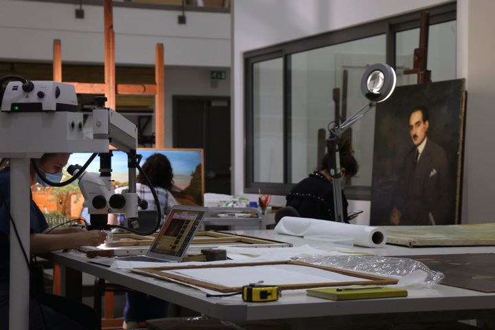 Sursock Museum workers are photographed in the lab restoring paintings.