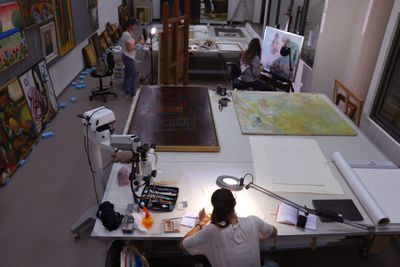 Sursock Museum workers are photographed in the lab repairing paintings.