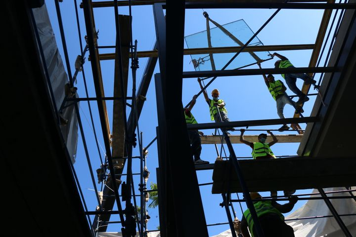 Construction workers are photographed from below as they repair the building of the Sursock Museum.