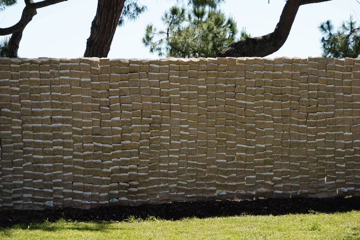 The installation 'Letters from Beirut' by T SAKHI (Tessa and Tara Sakhi) at the Venice Architecture Biennale is photographed from a distance. Beige-coloured pockets fill a wall that is outdoors, and in each pocket a letter is placed.