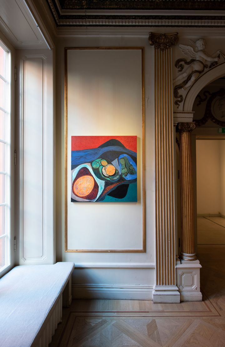 An abstract painting hangs next to a window in the gallery space.
