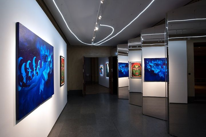 A gallery space shows a blue-hued painting of a female figure running in the moonlight, being chased by hooded figures.