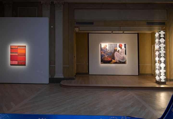 A darkened gallery space shows a lit up metallic totem, along with a painting of street vendors and to the far left, an abstract painting of bars of red, pink, yellow, and green.