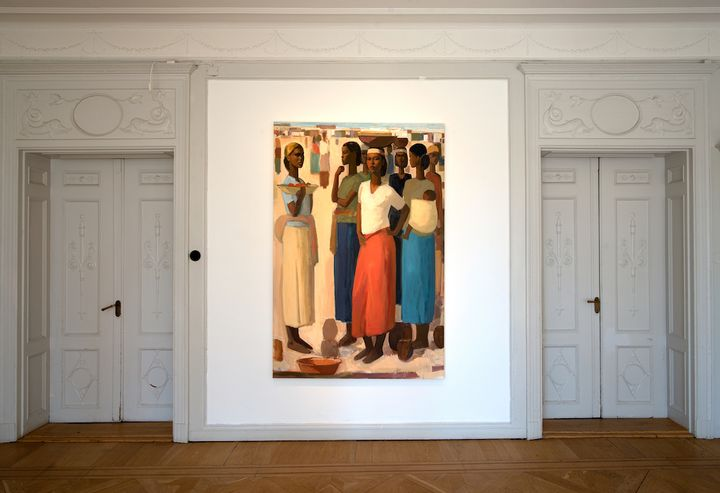 A group of women at a marketplace, with baskets balanced on their heads, takes up one wall in a white gallery space.