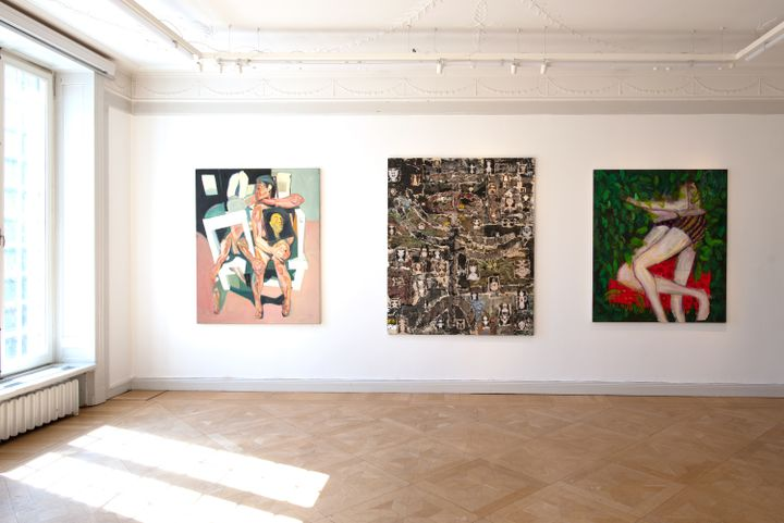 A series of three paintings hang on a wall in the gallery space, one depicting two entangled lovers alongside an abstract painting in shades of black and white, and a pink and black-hued painting of a figure sitting on a stool.