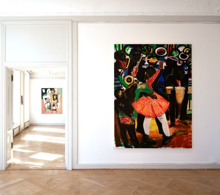 A large painting hanging in a white gallery shoes figures dancing and playing trumpets. In the background, the next-door room is visible, and on it a painting of a fragmentary painting of a figure sitting on a stool.