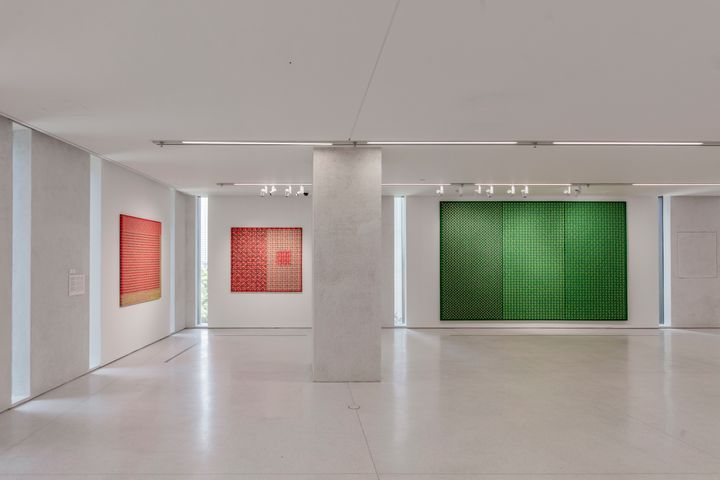 A series of three paintings in red and green are hang along the walls in a bright gallery space.