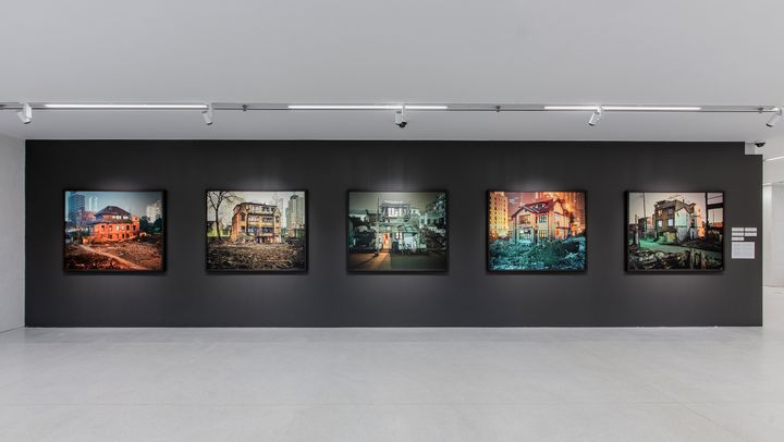 Five photographs by Greg Girard show houses amidst rubble and derelict settings, shot at nighttime.