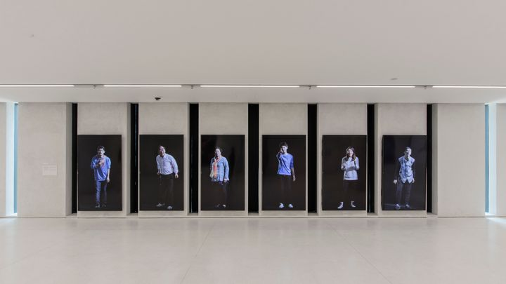 A six-channel video installation by Yang Zhenzhong features six different individuals standing upright on one screen each, each against a black background.