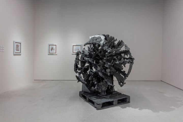 A cast zinc sculpture by Matthew Barney is spherical in structure, appearing to have parts missing from it. The sculpture is placed on a cast zinc wooden crate.