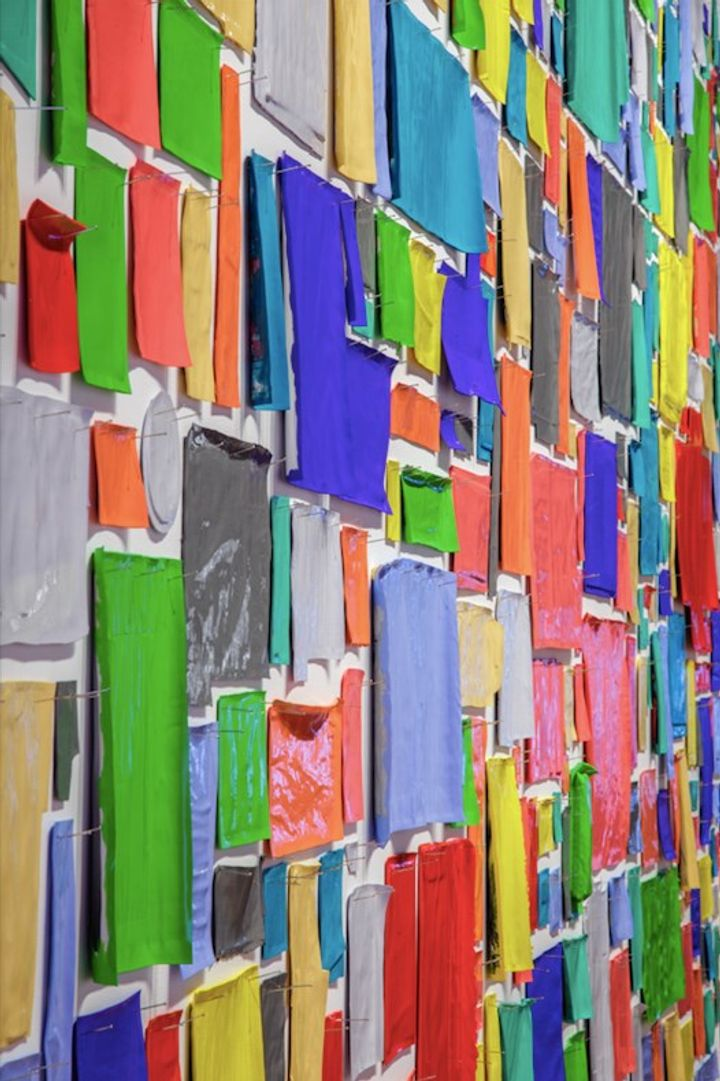 Rectangles of colourful paper are pinned to the wall and closely photographed, showing a sea of colour.