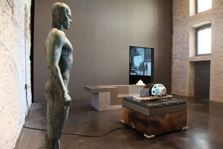 A statue of a figure stands erect in an exhibition space that also features machinic elements placed on pedestals.