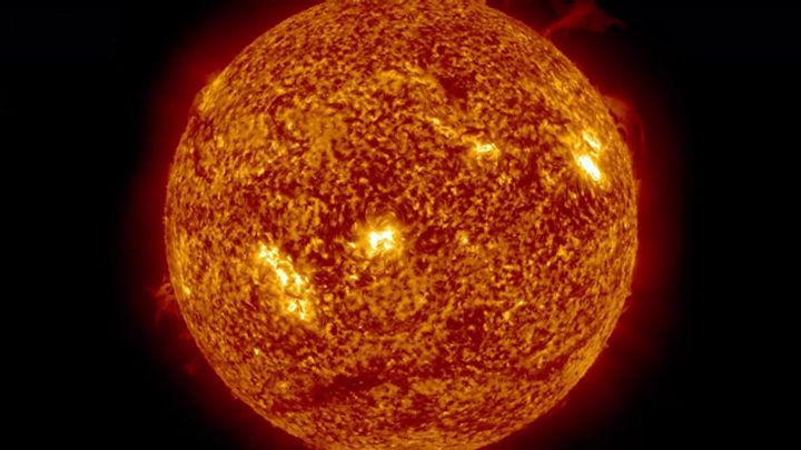 A closely cropped film still of the burning sun in outer space.