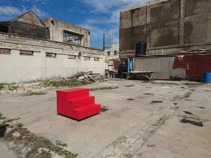 A set of three red stairs forming a block structure is placed in a barren environment.