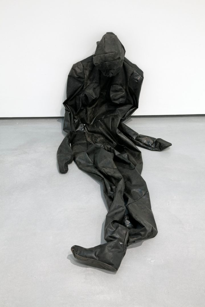 A black 'skin' in the shape of a human figure is placed slumped against a white wall in the gallery space.