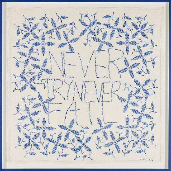 A square of embroidery featuring the words 'Never Try Never Fail' is surrounded by embroidered plant stems.