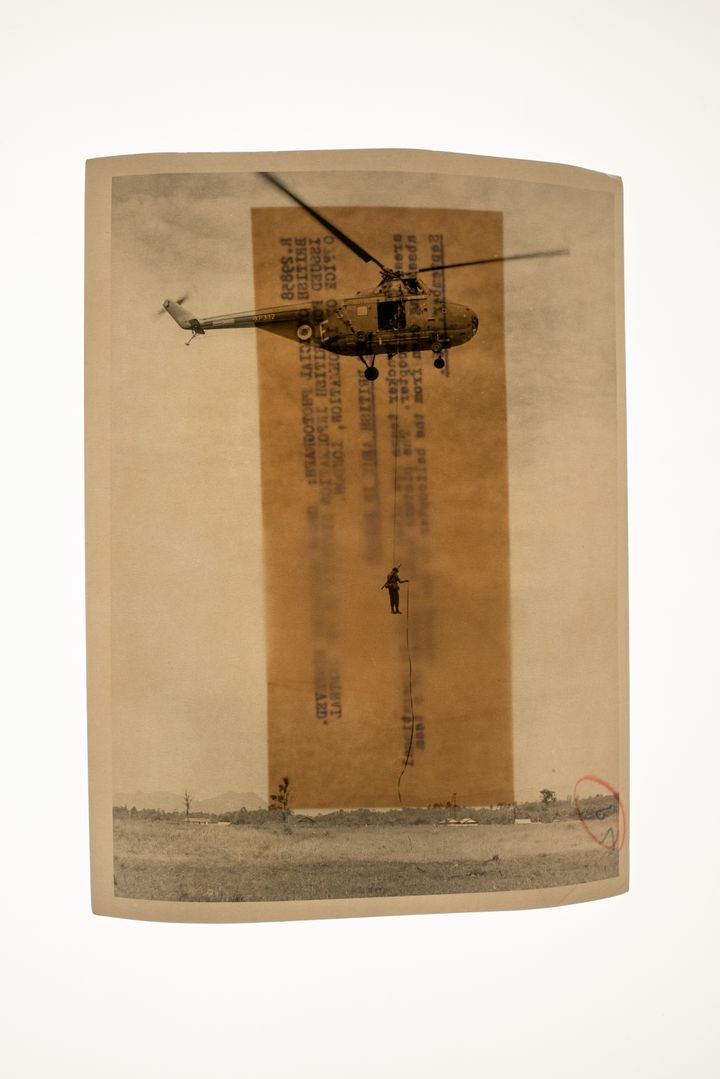A sepia archival photograph shows a figure descending from a helicopter on a piece of rope.