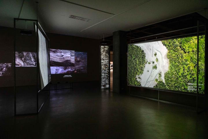 Multiple screens show aerial footage of landscapes, shown in a darkened exhibition space.