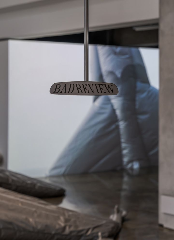 A rear-view mirror in the gallery space reads 'Bad Review'.