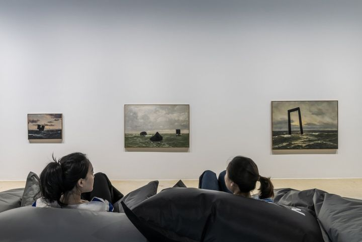 Two audience members sit on inflatable chairs in the gallery space, looking at three paintings on the gallery wall of seascapes, each featuring black geometric shapes sitting atop the waves and positioned on the horizon line.