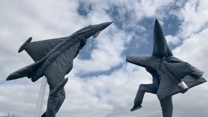Two figures with their bodies covered in decoy airplanes dance against a cloudy sky, in Fiona Banner aka The Vanity Press's film, Pranayama Organ.