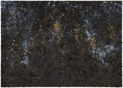 Gold, blue, and white pigments are speckled across a black cracking surface that resembles earth.
