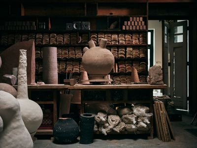 A photograph captures Theaster Gates' ceramics studio. In it, terracotta tiles are stacked in shelves, clay is wrapped in plastic and stacked below a workshop table, and some ceramic vessels are visible to the left.
