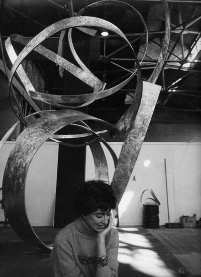 The artist Beverly Pepper is photographed in black and white in front of her sculpture. The sculpture, made up of curving lines, takes up most of the portrait frame, while the artist sits beneath it smiling while looking towards the floor, her chin in her hands.