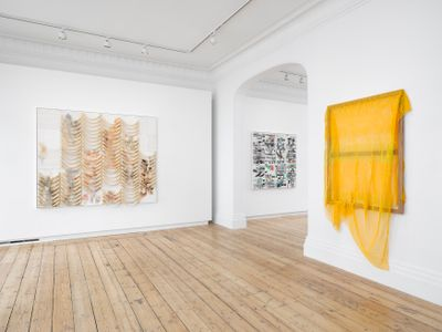 Three beaded 'paintings' by Liza Lou are hanging against white walls of the gallery space. Yellow beads drip from the artist's work to the right, while Lou's canvas to the left is made up of bands of beige beads.