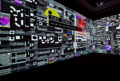 An installation by Peter Burr covers the walls of a gallery space with glitches and television static.
