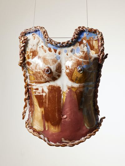 A ceramic torso by Phoebe Collings-James is layered with tones of brown, creme white,  yellow, and light blue.