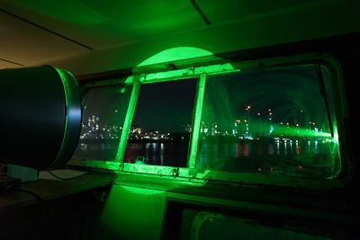 A green light is emitted from the window of a lighthouse, pictured from its interior beaming out towards the Thames River.