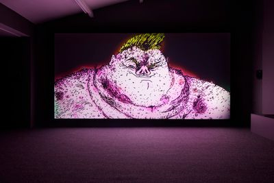 A grotesque figure with the nose of a pig is visible in a video installation in a darkened space, their large, hairy, and pink torso glowing pink out towards the room.