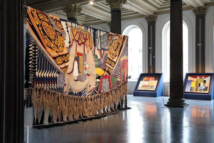 A large tapestry is hanging from the ceiling an a gallery space that features columns, while smaller tapestries, each one featuring colourful geometric patterns, are to the far right-hand side of the room.