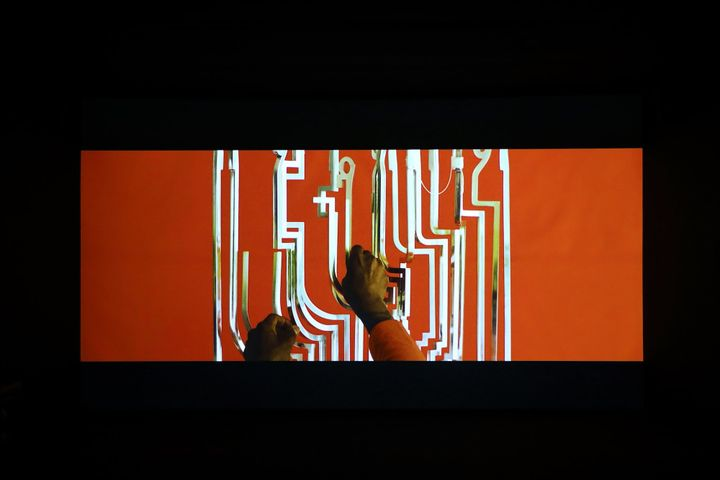 Silver geometric forms are pictured in a video still, showing from a screen in a darkened gallery space. Hands above the geometric shapes seem to interfere with them.