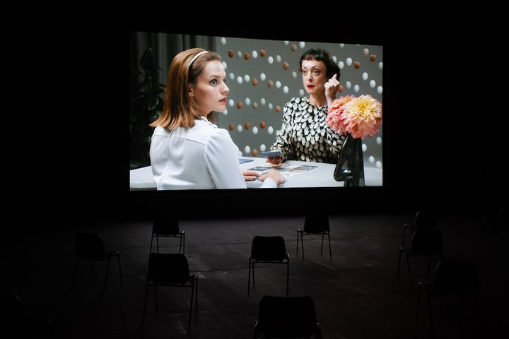 A film screen shows two women sitting at a table adorned with a flower in a vase. One holds a cigarette and looks forward, while the figure in the foreground looks across her shoulder and off to the right.