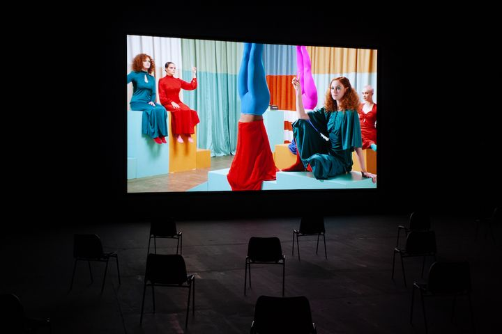 A group of women on a film set draped in colourful fabric, are also wearing colourful clothes and sit around one figure who is standing on their head. The film is shown in a darkened gallery space.