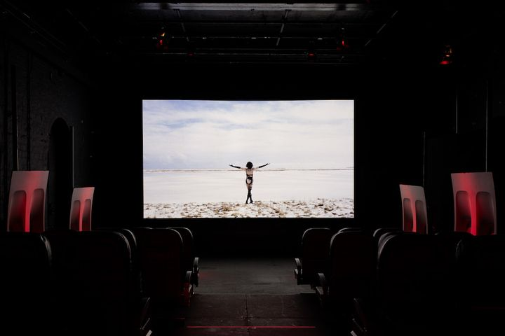 A video screen in a darkened gallery space features a figure walking towards the horizon in a barren landscape, their arms raised in the air.