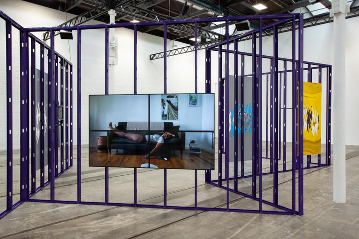 A purple metallic structure forms an installation by Martine Syms showing in a gallery space, with video screens hanging from it. One screen features a woman lying on a sofa.