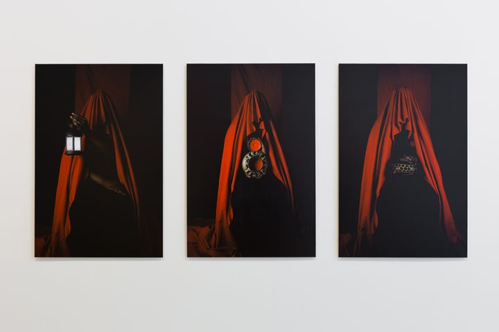 Three photographs hanging on a white wall each figure draping red fabric, from beneath which hands offer up objects such as a lamp and a mirror.