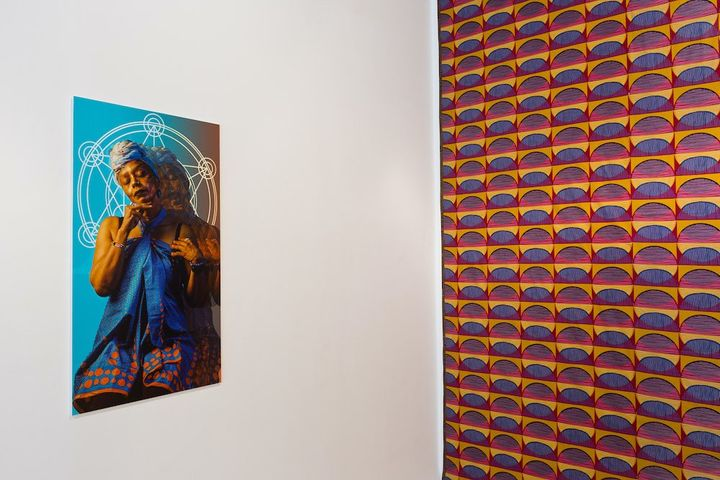 An installation photograph features patterned wallpaper pasted on a wall to the right, with a portrait of a figure hanging on the wall to the left.