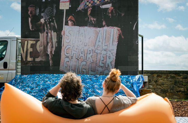 Two members of the public are sitting on an inflatable chair outdoors, viewing a screen in front of them.