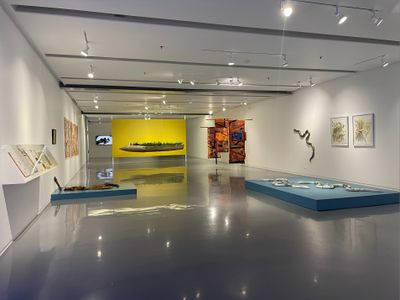 A colourful display of artworks in a white exhibition space includes a short, flat sky-blue podium with ceramic snakes on it to the right of the frame, and a yellow wall in the distance with a losenge-shaped sculpture hanging in front of it, with plants arranged along its centre.