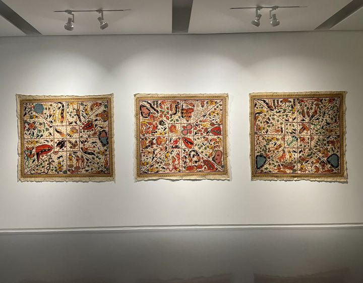 Three paintings on tapestry by Citra Sasmita feature cosmic, hyper-detailed paintings of women and snakes, arranged in concentric squares as a grid.
