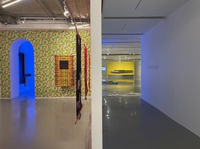 A photograph features a wall partitioning a corridor and a gallery space to the left, which is covered in floral wallpaper, upon which tapestries are placed.