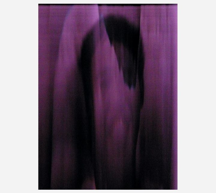 An eerie purple print of a elongated portrait by artist Komtouch Dew Napattaloong.