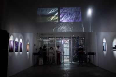 An opening of an exhibition where the gallery space is darkened to feature artworks and video projections.