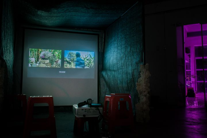 A darkened gallery space features short red stools that are placed in front of a video projection.